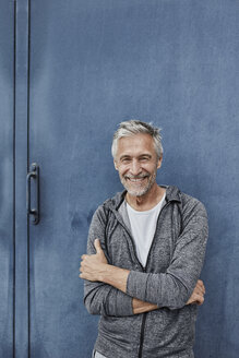 Portrait of laughing mature man standing in front of gym - RORF01737
