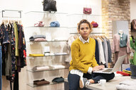 Young woman working in fashion store, using laptop - PESF01381