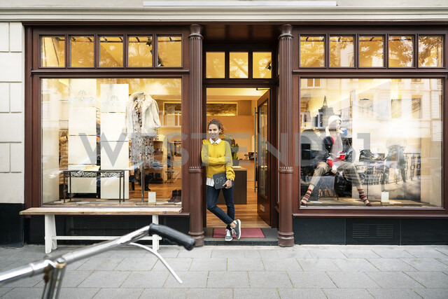 Young woman standing in door of a fashion store, holding laptop - PESF01390 - Peter Scholl/Westend61