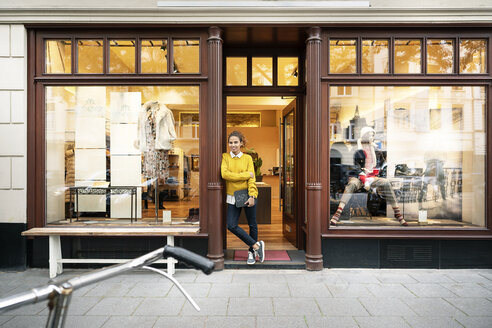 Young woman standing in door of a fashion store, holding laptop - PESF01390