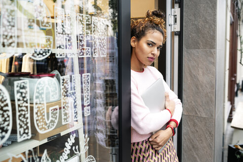 Young woman standing in door of a fashion store, holding laptop - PESF01402
