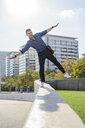 Portrait of man balancing on wall - GIOF05720