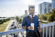 Portrait of smiling man with coffee to go and headphones leaning on railing of bridge - GIOF05729