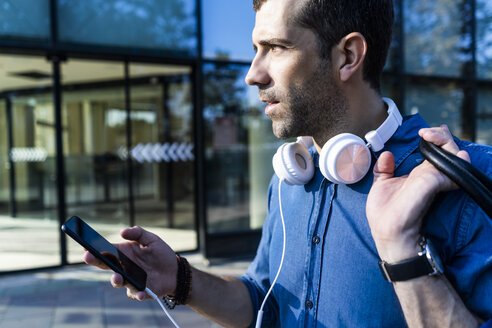 Profile of man with headphones and mobile phone looking at distance - GIOF05741