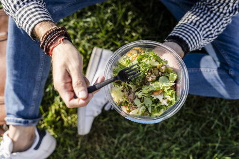 Man sitting on a meadow eating mixed salad, partial view - GIOF05744