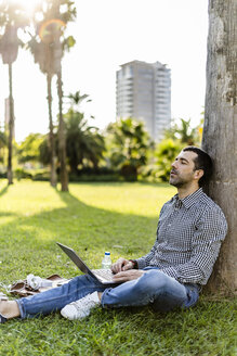 Man with laptop leaning against tree trunk on meadow in city park relaxing - GIOF05756
