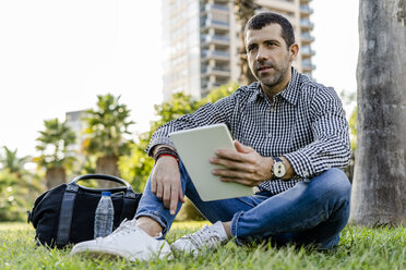Portrait of man with digital tablet sitting on meadow in city park thinking - GIOF05759