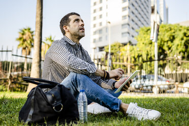 Man sitting on meadow in city park with digital tablet looking up - GIOF05762