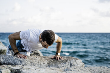 Man doing doing pushups on rock in front of the sea - GIOF05774