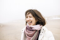 Portrait of laughing woman on the beach - KMKF00751