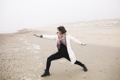Woman doing yoga exercise on the beach - KMKF00757