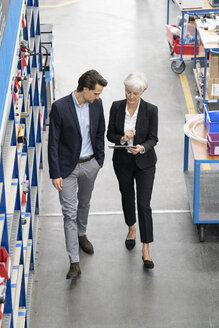 Businessman and senior businesswoman with tablet walking in a factory - DIGF05646