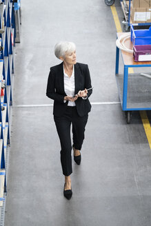 Senior businesswoman with tablet walking in a factory - DIGF05649