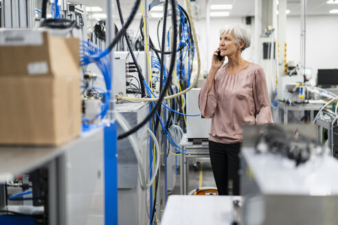 Senior woman on cell phone in a factory - DIGF05661