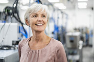 Portrait of smiling senior woman in a factory - DIGF05664