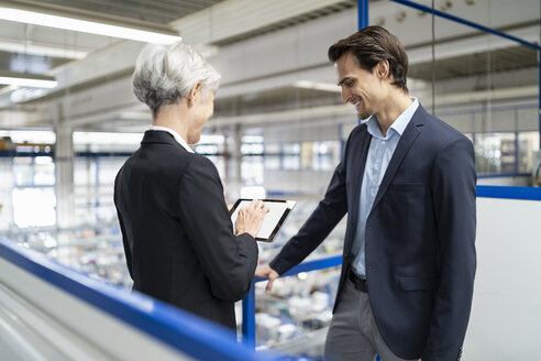 Smiling businessman and senior businesswoman with tablet talking in a factory - DIGF05679
