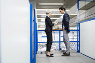 Businessman and senior businesswoman with tablet talking in a factory - DIGF05682