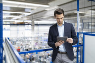 Businessman using tablet in a factory - DIGF05685