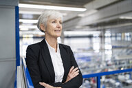 Confident senior businesswoman in a factory looking around - DIGF05697