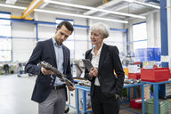 Businessman and senior businesswoman examining workpiece in a factory - DIGF05706