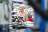 Senior woman using tablet in a factory - DIGF05715