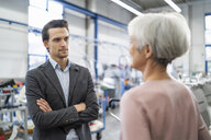 Smiling businessman and senior businesswoman talking in a factory - DIGF05721