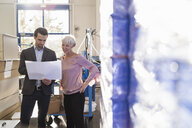 Businessman and senior woman looking at plan in a factory - DIGF05727