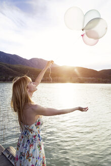 Young woman wearing summer dress with floral design standing on jetty looking at balloons - JSRF00110