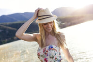 Smiling young woman wearing summer hat and top with floral design in front of lake - JSRF00113