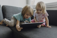 Brother and little sister using digital tablet on the couch at home - JLOF00303