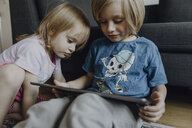 Brother and little sister sitting on the floor at home using digital tablet - JLOF00306