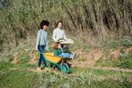 Family walking on a dirt track, pushing wheelbarrow, carrying crate with vegetables - GEMF02706