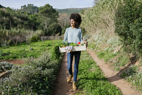 Woman walking in the field, carrying a vegetable crate - GEMF02787