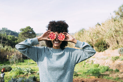 Woman standing in the countryside, covering eyes with halved pomegranates - GEMF02826