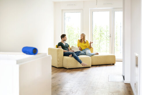Couple sitting on couch in their new home, discussing - PESF01422