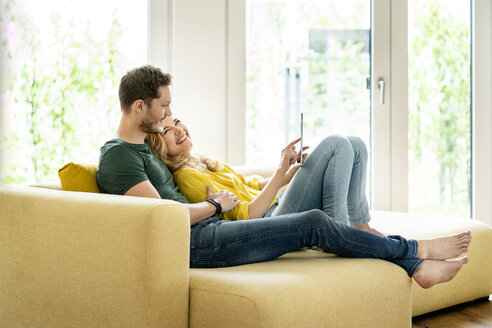 Couple sitting on couch in their new home, using digital tablet - PESF01428