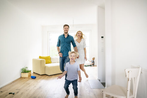Happy family moving into their new home, parents chasing son - PESF01437