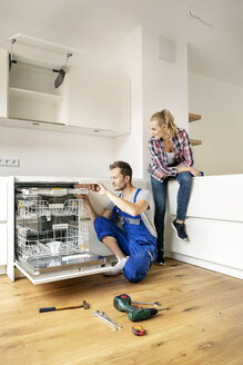 Couple fitting dishwasher in their new built-in kitchen - PESF01449