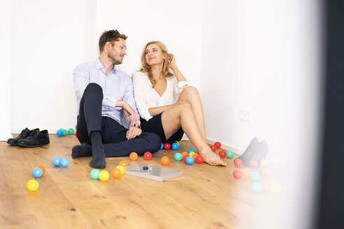 Business couple sitting on floor of their new home with colorful balls - PESF01473