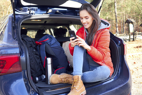 Poland, Polish Jura, Woman sitting in car trunk during road trip and using smartphone - BSZF00901