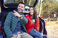 Couple pointing and looking away while sitting in car trunk during road trip - BSZF00904