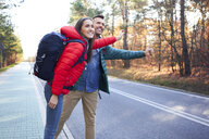 Happy couple hitchhiking road in the woods during backpacking trip - BSZF00907