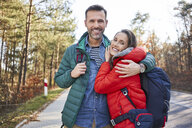 Portrait of happy couple embracing on a road in the woods during backpacking trip - BSZF00913