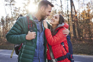 Happy couple embracing on a road in the woods during backpacking trip - BSZF00916