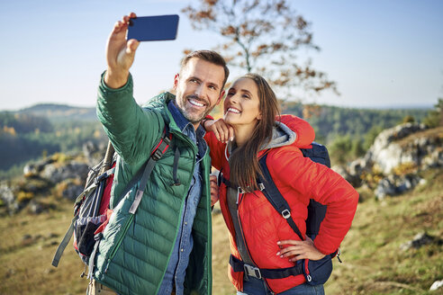 Poland, Polish Jura, Couple taking selfie while hiking in the hills on sunny autumn day - BSZF00922