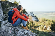 Woman on a hiking trip in the mountains resting on a rock - BSZF00925