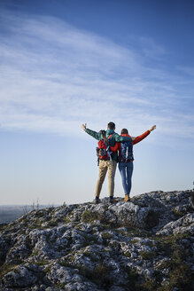 Happy couple on a hiking trip in the mountains standing on rock enjoying the view - BSZF00937
