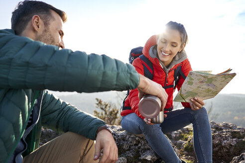 Happy couple on a hiking trip in the mountains drinking hot drink during a break - BSZF00940