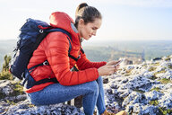 Woman on a hiking trip in the mountains sitting on rock checking cell phone - BSZF00943