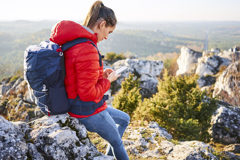 Woman on a hiking trip in the mountains checking cell phone - BSZF00949